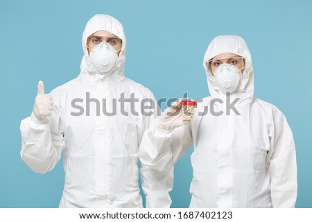 People in protective suits respirator masks hold drugs isolated on blue background studio. Epidemic pandemic new rapidly spreading coronavirus 2019-ncov from Wuhan China, medicine flu virus concept #1687402123