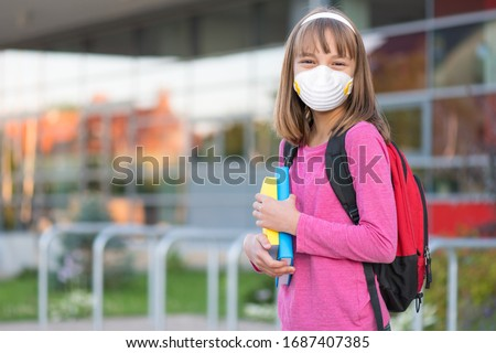 Concept of coronavirus COVID-19. Schoolgirl wearing medical face mask to health protection from influenza virus. Student girl with backpack and books - outdoors portrait. Child back to to school. #1687407385