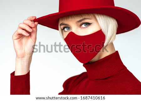 Woman wearing trendy fashion outfit during quarantine  of coronavirus outbreak. Total red look including protective stylish handmade face mask  #1687410616