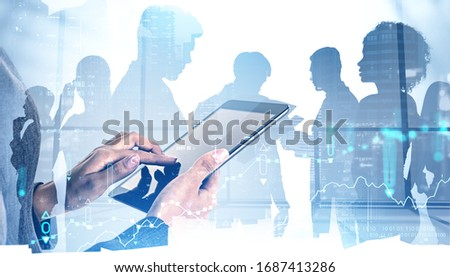 Hands of woman trader using tablet computer in blurry office with double exposure of digital graphs and night cityscape with diverse business team. Concept of stock market and teamwork. Toned image #1687413286