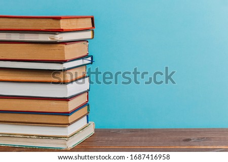 A simple composition of many hardback books, raw books on a wooden table and a bright blue background. back to school. Education. #1687416958