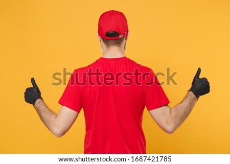 Back rear view delivery man in red cap blank t-shirt uniform gloves isolated on yellow background studio Guy employee working courier Service quarantine pandemic coronavirus virus 2019-ncov concept #1687421785