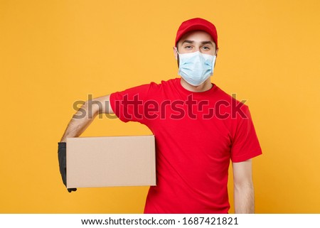 Delivery man employee in red cap blank t-shirt uniform face mask gloves hold empty cardboard box isolated on yellow background studio Service quarantine pandemic coronavirus virus 2019-ncov concept #1687421821