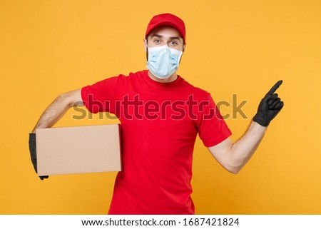 Delivery man employee in red cap blank t-shirt uniform face mask gloves hold empty cardboard box isolated on yellow background studio Service quarantine pandemic coronavirus virus 2019-ncov concept #1687421824