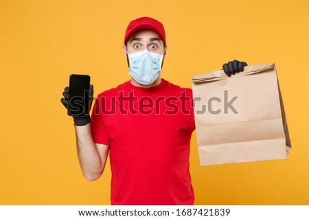 Delivery man employee in red cap blank t shirt uniform mask glove hold craft paper packet cellphone isolated on yellow background studio Service quarantine pandemic coronavirus virus 2019-ncov concept #1687421839