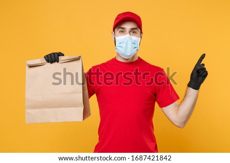 Delivery man employee in red cap t-shirt uniform mask glove hold craft paper packet with food isolated on yellow background studio Service quarantine pandemic coronavirus virus 2019-ncov concept #1687421842