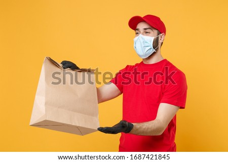 Delivery man employee in red cap t-shirt uniform mask glove hold craft paper packet with food isolated on yellow background studio Service quarantine pandemic coronavirus virus 2019-ncov concept #1687421845