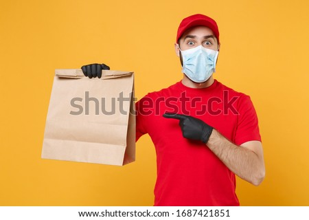 Delivery man employee in red cap t-shirt uniform mask glove hold craft paper packet with food isolated on yellow background studio Service quarantine pandemic coronavirus virus 2019-ncov concept #1687421851