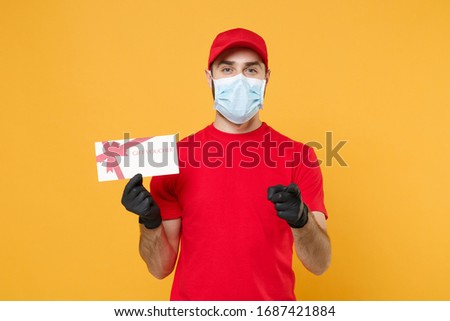 Delivery man red cap blank t-shirt uniform sterile mask gloves isolated on yellow background studio Guy employee working courier hold certificate Service pandemic coronavirus virus 2019-ncov concept #1687421884