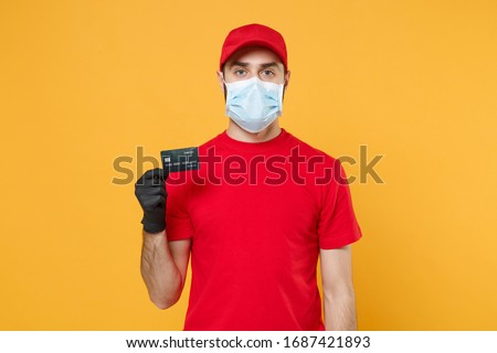 Delivery man red cap blank t-shirt uniform mask gloves isolated on yellow background studio Guy employee work courier hold credit card Service quarantine pandemic coronavirus virus 2019-ncov concept #1687421893