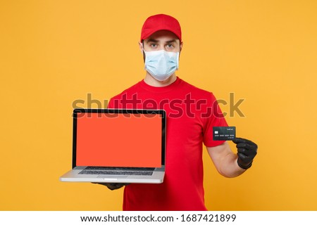Delivery man in red cap blank t-shirt uniform mask gloves isolated on yellow background studio Guy employee work hold laptop computer Service quarantine pandemic coronavirus virus 2019-ncov concept #1687421899