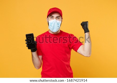 Delivery man in red cap blank t-shirt uniform sterile face mask gloves isolated on yellow background studio Guy courier hold mobile phone Service quarantine pandemic coronavirus 2019-ncov concept #1687421914