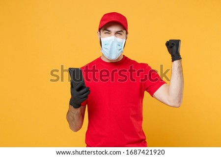 Delivery man in red cap blank t-shirt uniform sterile face mask gloves isolated on yellow background studio Guy courier hold mobile phone Service quarantine pandemic coronavirus 2019-ncov concept #1687421920
