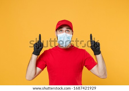 Delivery man in red cap blank t-shirt uniform sterile face mask gloves isolated on yellow background studio Guy employee working courier Service quarantine pandemic coronavirus virus concept #1687421929