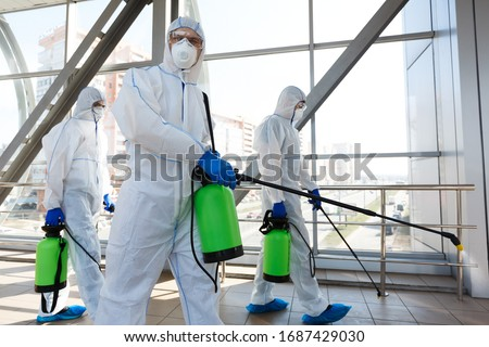 Professional workers in hazmat suits disinfecting indoor accommodation, pandemic health risk, coronavirus #1687429030