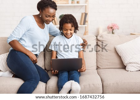 Distance Education Concept. African mother helping her child with homework, using laptop, sitting on sofa at home. Free space