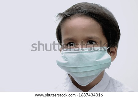 Medan, North Sumatra, Indonesia - MARCH 2020: Boy wearing hygienic mask to prevent the virus PM2.5 and Coronavirus or COVID-19. People in masks The outbreak of Novel COVID-19 in Wuhan China. air pollu #1687434016