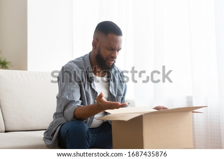 Disappointed african american guy with buying in box, copy space #1687435876