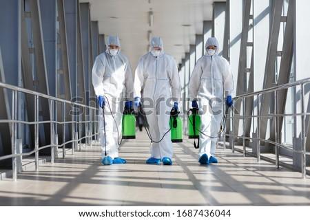 People in protective hazmat suits carrying barrels, pathogen respiratory quarantine coronavirus concept, copy space #1687436044