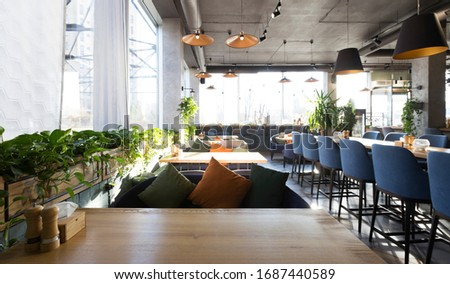 Empty restaurant interior while coronavirus pandemic, no people, soft sofas with pillows, copy space Royalty-Free Stock Photo #1687440589