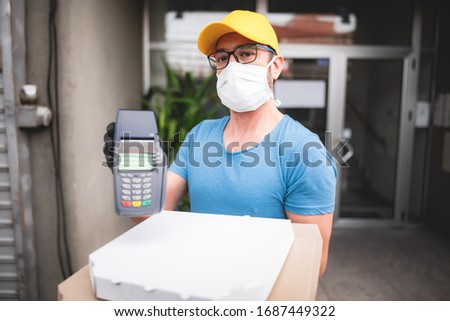 Deliveryman with protective medical mask holding pizza box and POS wireless terminal for card paying - days of viruses and pandemic, food delivery to your home and safety hygiene measures. #1687449322