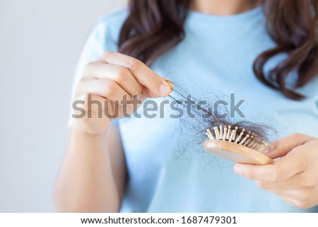 young woman worried about Hair loss problem, hormonal disbalance, stress concept. Many hair fall after combing in hair brush in hand. Female untangled her hair with a comb, Health care #1687479301