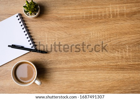 desk office with blank notepad, coffee cup and pen on wood table. Flat lay top view copy spce. #1687491307