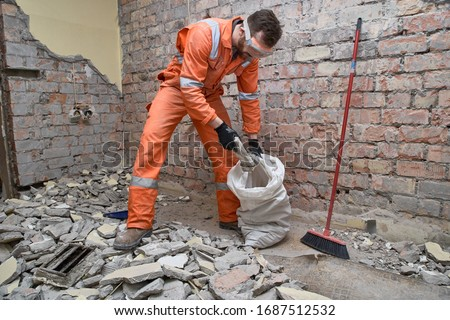 Builder cleaning room after demolition jobs, from old concrete by collecting it in sugar bags. #1687512532