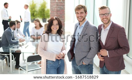 three young employees standing in a modern office. #1687518829