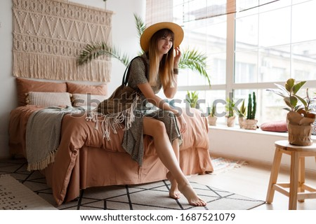 Indoor portrait of pretty woman in  dress  enjoying  cozy home atmosphere. Boho lifestyle, plants and macrame on wall.  #1687521079