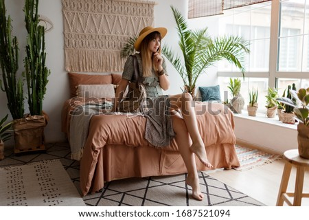 Indoor portrait of pretty woman in dress  enjoying  cozy home atmosphere. Boho lifestyle. Home plants and macrame on wall.  #1687521094