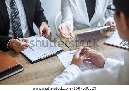 Employer or committee holding reading a resume with talking during about his profile of candidate, employer in suit is conducting a job interview, manager resource employment and recruitment concept. Royalty-Free Stock Photo #1687530523