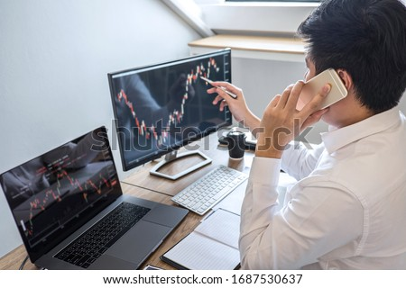 Stock exchange market concept, Business investor trading or stock brokers having a planning and analyzing with display screen and pointing on the data presented and deal on a stock exchange. #1687530637