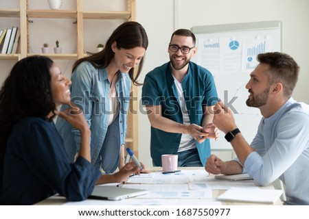 Smiling diverse colleagues gather in boardroom brainstorm discuss financial statistics together, happy multiracial coworkers have fun cooperating working together at office meeting, teamwork concept Royalty-Free Stock Photo #1687550977