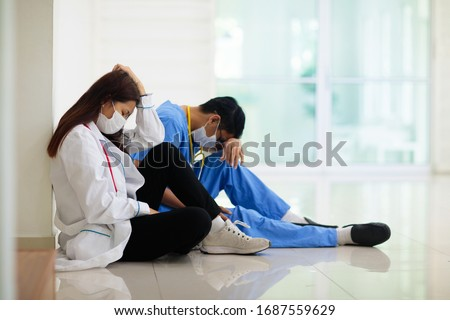 Exhausted tired Asian doctor or nurse. Virus outbreak in Asia. Coronavirus pandemic. Clinic and hospital medical stuff working over hours. Overworked professional. Stress and depression. #1687559629
