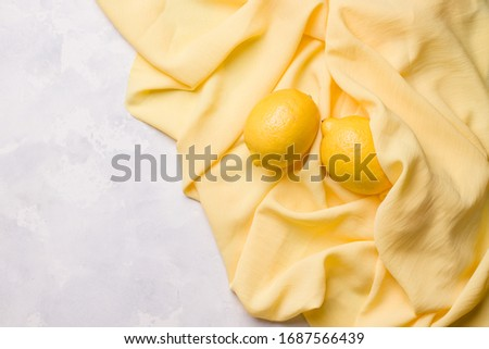 lemons lie on a yellow cloth on a concrete background. copy space #1687566439