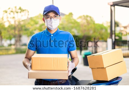 Deliveryman of goods and parcels to customers by protecting them with medical masks and gloves / Online shopping order under quarantine coronavirus covid-19 #1687628281
