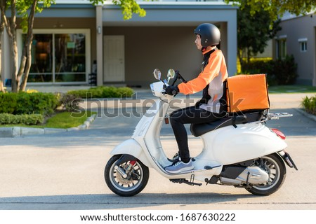 Asian man courier on scooter delivering food in town streets with a hot food delivery from take aways and restaurants to home, express food delivery and shopping online concept. #1687630222