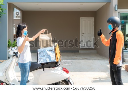 Asian woman pick up delivery food bag from box and thumb up form contactless or contact free from delivery rider with bicycle in front house for social distancing for infection risk. #1687630258