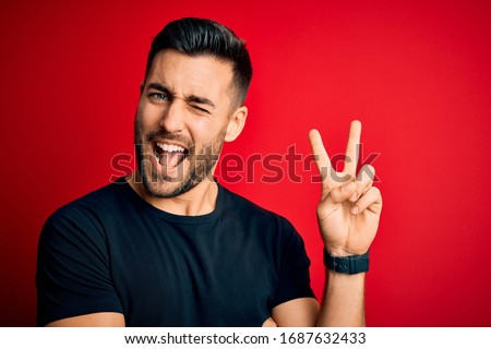 Young handsome man wearing casual black t-shirt standing over isolated red background smiling with happy face winking at the camera doing victory sign. Number two.