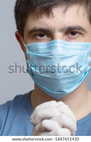 close up face of a serious young doctor in protective medical mask with surgical gloves on gray studio background, concept medicine and health #1687651420
