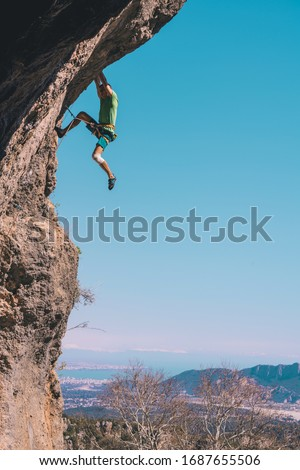 Athletic man climbs an overhanging rock with rope, lead climbing in Turkey. Sport climbing outdoor. #1687655506