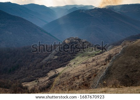 epic landscape with ruins of a castle and heavenly lights at sunset. Liteni fortress in Transylvania. #1687670923