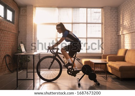 Asian woman cyclist. She is exercising in the house.By cycling on the trainer and play online bike games #1687673200