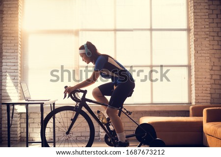 Asian woman cyclist. She is exercising in the house.By cycling on the trainer and play online bike games Royalty-Free Stock Photo #1687673212