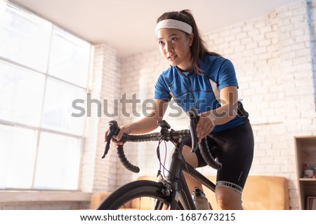 Asian woman cyclist. She is exercising in the house.By cycling on the trainer and play online bike games #1687673215