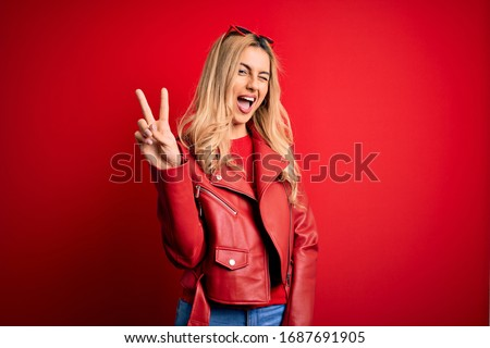 Young beautiful blonde woman wearing casual jacket standing over isolated red background smiling with happy face winking at the camera doing victory sign. Number two.
