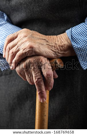 Closeup of senior woman's hands on wooden walking stick  #168769658