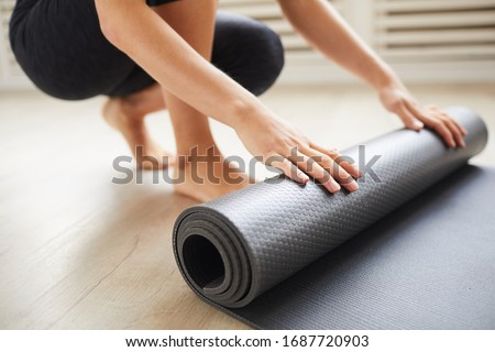 Close-up of young woman with exercise mat preparing for sports training Royalty-Free Stock Photo #1687720903