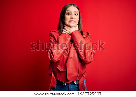 Young beautiful brunette woman wearing casual jacket standing over red background shouting and suffocate because painful strangle. Health problem. Asphyxiate and suicide concept. #1687725907